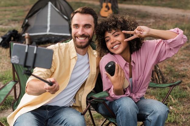 Casal sorridente tirando uma selfie enquanto acampa ao ar livre