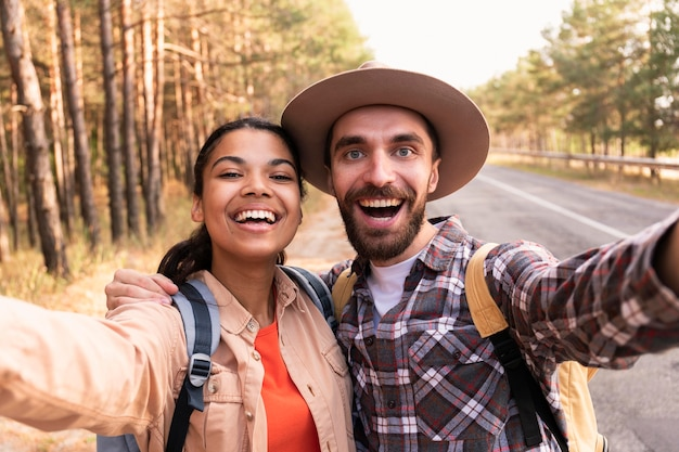 Casal sorridente tirando uma selfie enquanto viaja