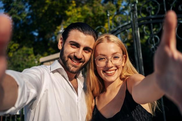 Casal sorridente tirando uma selfie