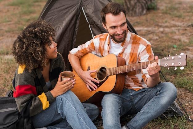 Casal sorridente tocando guitarra enquanto acampa do lado de fora