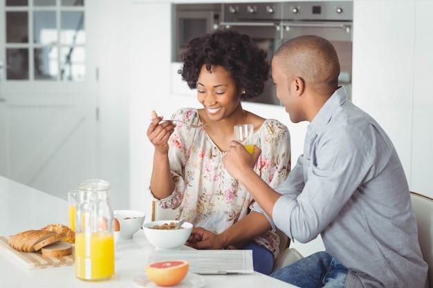 Casal sorridente tomando café da manhã juntos na cozinha
