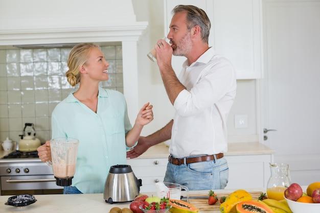 Casal sorridente tomando suco na cozinha em casa