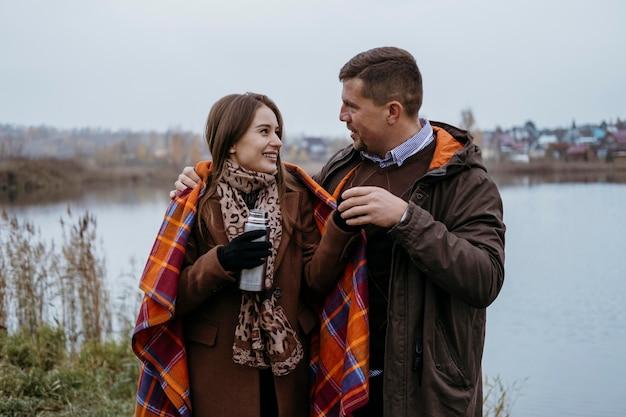 Casal sorridente tomando uma bebida quente à beira do lago com cobertor