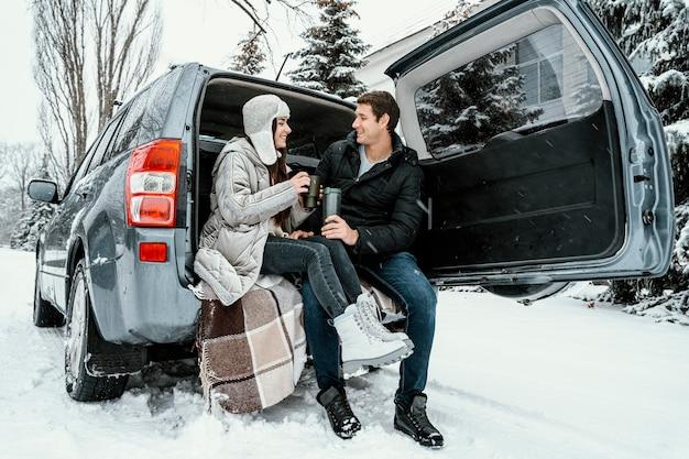 Casal sorridente tomando uma bebida quente no porta-malas do carro durante uma viagem