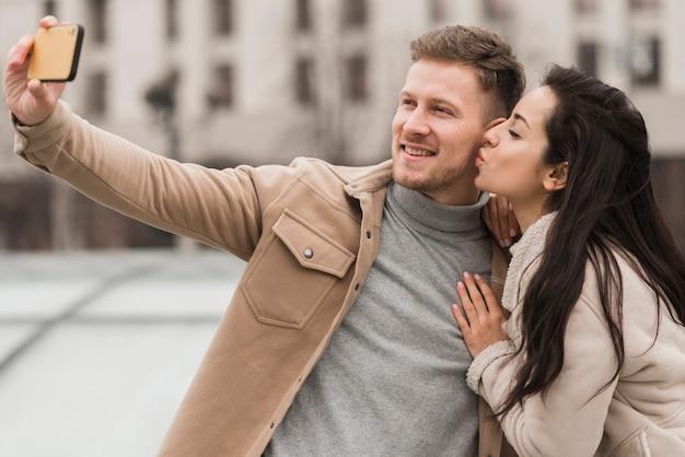 Casal sorridente tomando uma selfie