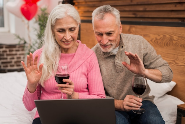 Casal sorridente usando laptop e bebendo vinho