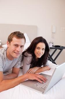 Casal sorridente usando laptop no quarto juntos