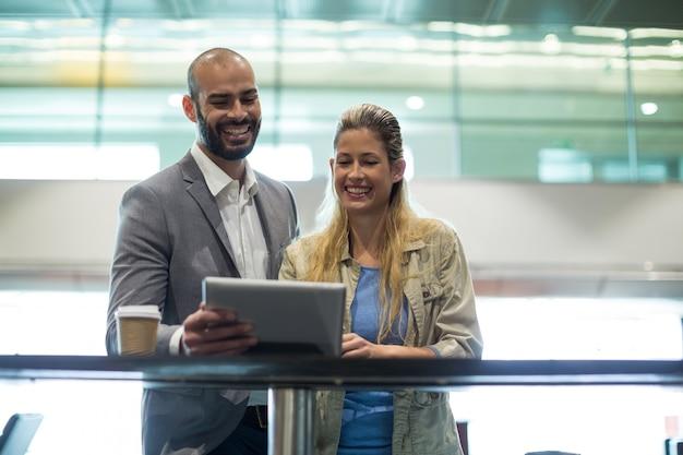 Casal sorridente usando tablet digital na sala de espera