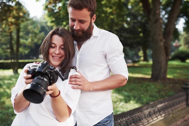 Casal sorridente, vendo fotos na câmera.