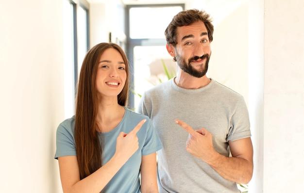 Casal sorrindo alegremente, mulher se sentindo feliz e apontando para o lado e para cima, mostrando o objeto no espaço da cópia