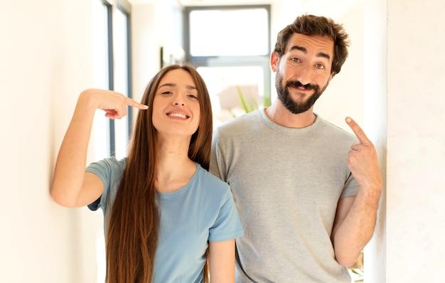Casal sorrindo com confiança apontando para o próprio sorriso largo, atitude positiva, relaxada e satisfeita