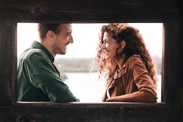 Casal sorrindo de lado olhando uns para os outros