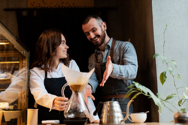 Casal sorrindo e apontando para o filtro de café