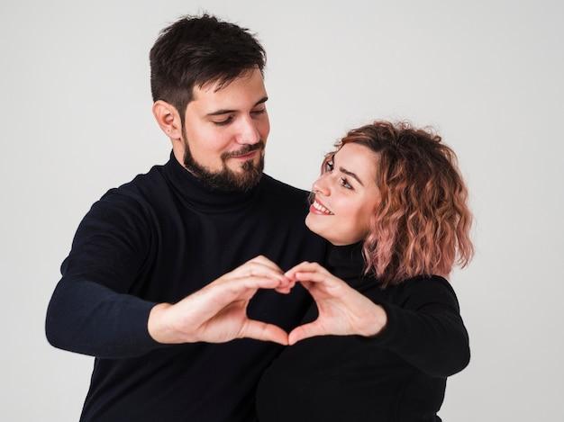 Casal sorrindo e fazendo formato de coração com as mãos