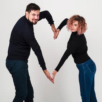 Casal sorrindo e fazendo formato de coração com braços
