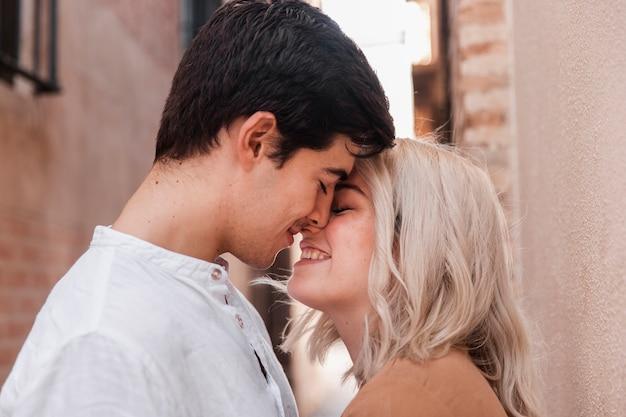 Casal sorrindo e indo para um beijo