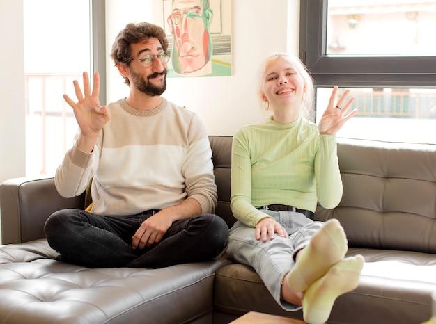 Casal sorrindo e mulher parecendo amigável, mostrando o número quatro ou o quarto com a mão para a frente, em contagem regressiva