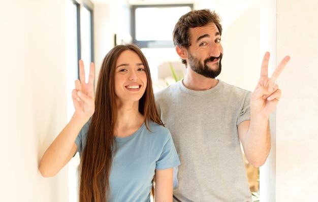 Casal sorrindo e parecendo amigável, mostrando o número dois ou o segundo com a mão para a frente, em contagem regressiva