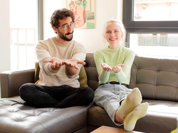 Casal sorrindo feliz com olhar amigável, confiante e positivo, oferecendo e mostrando um objeto ou conceito