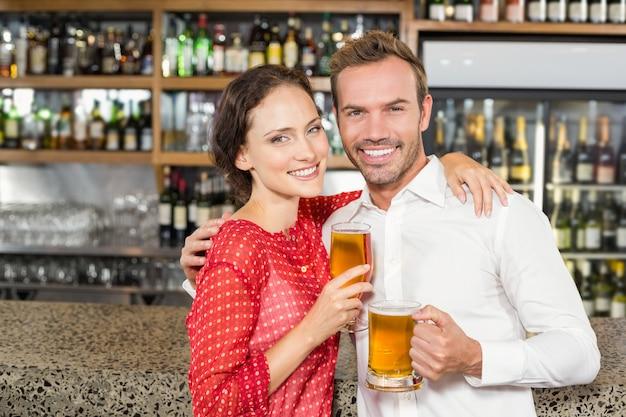 Casal sorrindo para a câmera e segurando cervejas