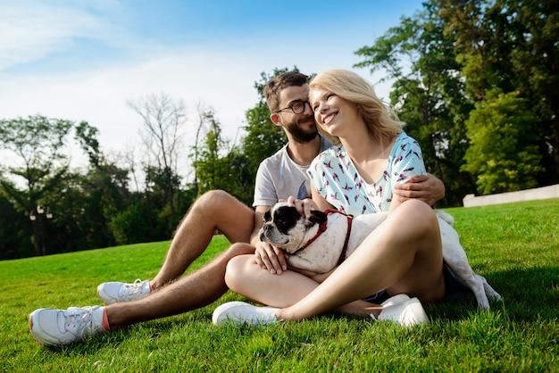 Casal sorrindo, sentado na grama com bulldog francês no parque