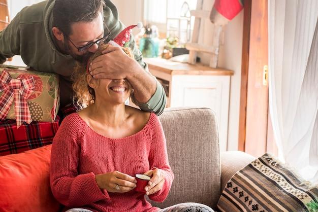 Casal surpresa presente de natal com homem fazendo uma surpresa para a esposa mulher em casa nas férias