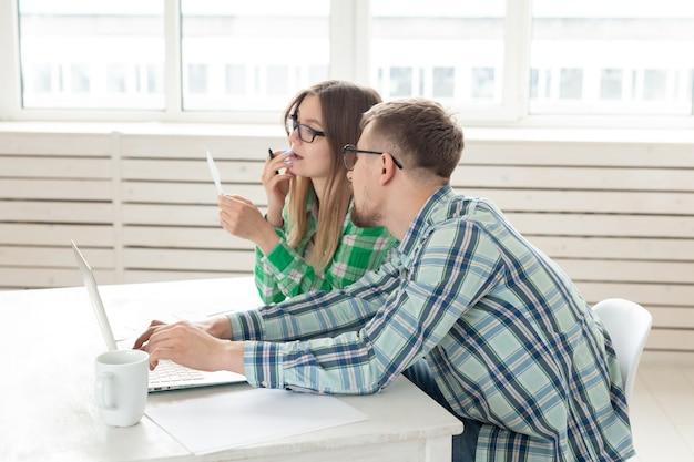 Casal surpreso. marido e mulher estão considerando as contas para pagar um apartamento e estão chocados com o valor recebido, anotando os resultados em suas contas domésticas em um laptop.
