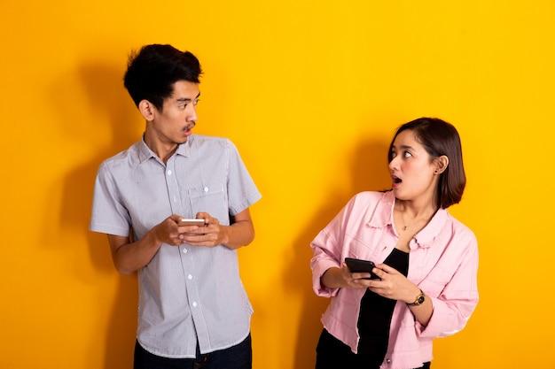 Casal surpreso olhando um ao outro enquanto segura o telefone