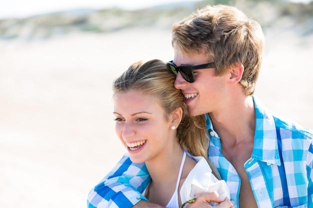 Casal teen loira abraça juntos na praia ao ar livre