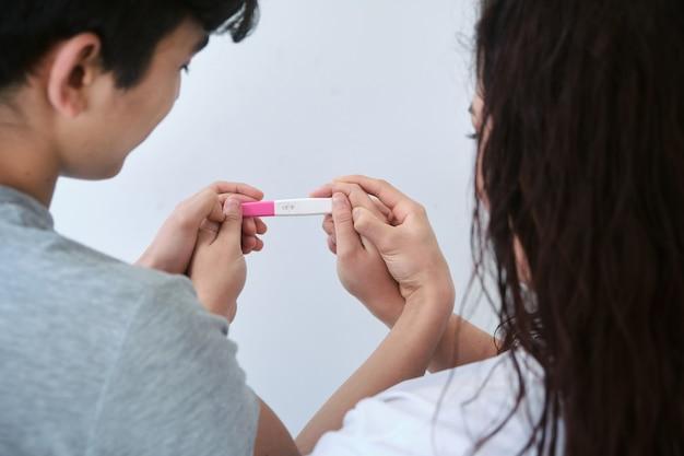 Casal tem nas mãos um teste de gravidez.