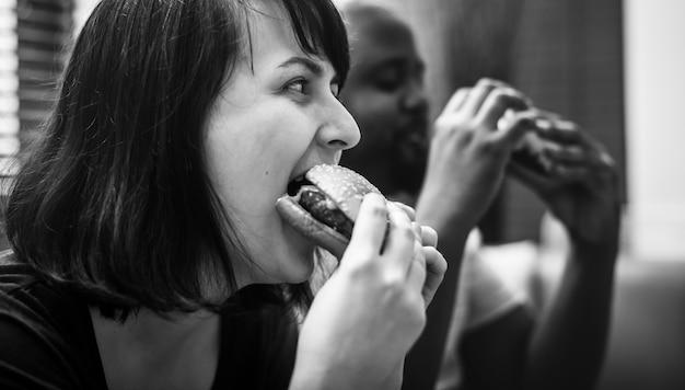 Casal tendo fast food no sofá