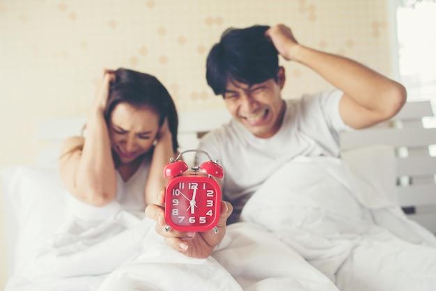 Casal tendo problemas em acordar cedo de manhã na cama