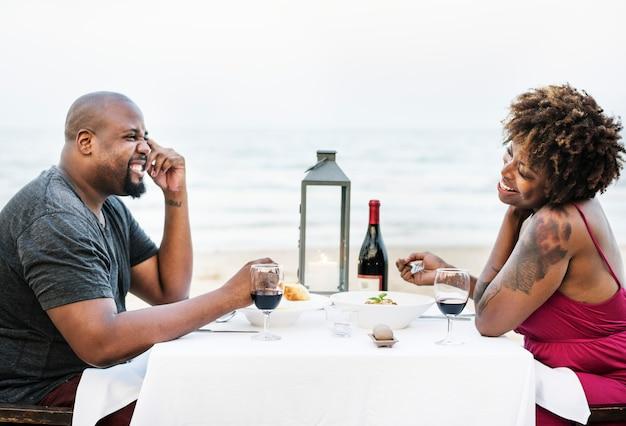 Casal tendo um jantar romântico na praia