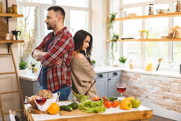 Casal tendo uma briga. homem e mulher estão repreendendo em pé na cozinha