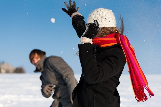 Casal tendo uma luta de bolas de neve no inverno