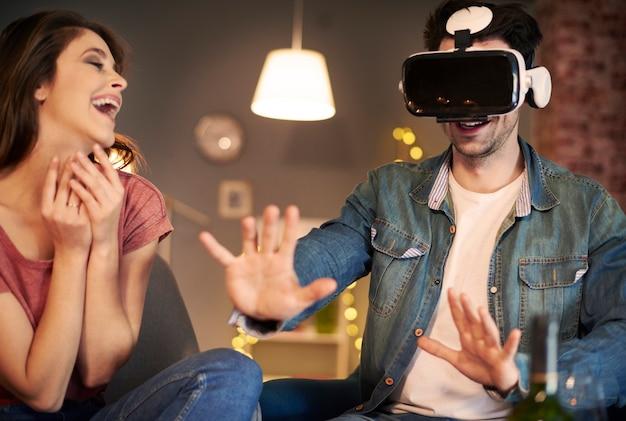 Casal testando óculos de realidade virtual em casa