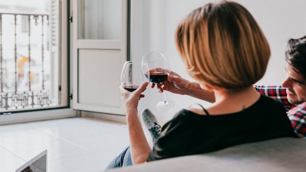 Casal tingindo vinho tinto no sofá