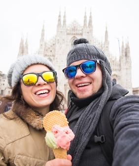Casal tira foto de selfie com sorvete em frente à catedral duomo de milão.