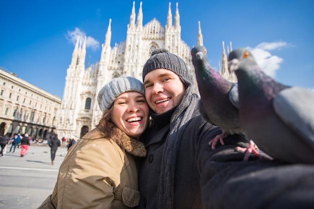 Casal tirando auto-retrato com pombo na praça duomo em milão. viagem de inverno, itália e conceito de relacionamento