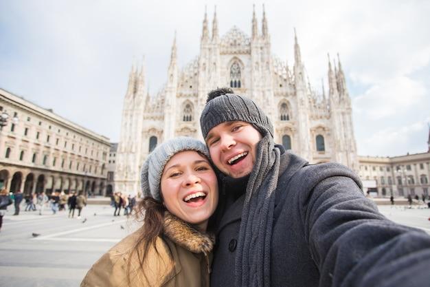 Casal tirando auto-retrato na praça duomo em milão. viagem de inverno, itália e conceito de relacionamento