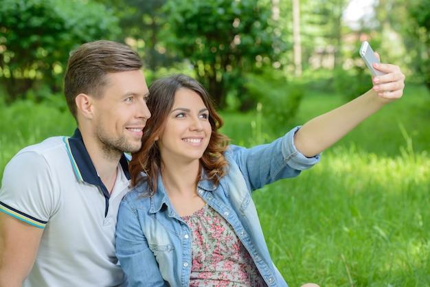 Casal tirando foto de si mesmo com telefone inteligente.