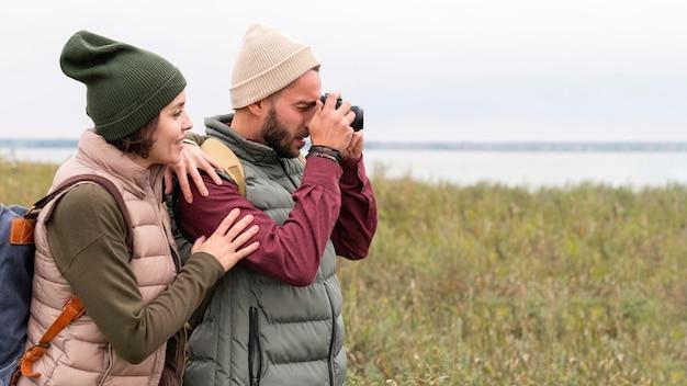 Casal tirando fotos na natureza