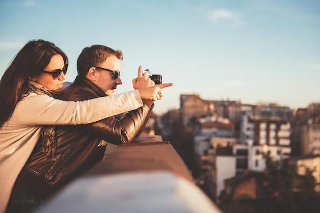 Casal tirando fotos no telhado