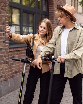 Casal tirando selfie com scooters ao ar livre
