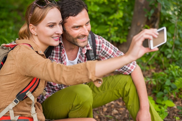 Casal tirando selfie na floresta