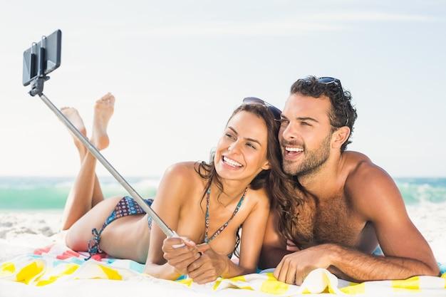 Casal tirando selfie na praia
