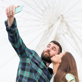 Casal tirando uma selfie enquanto se beijando ao ar livre