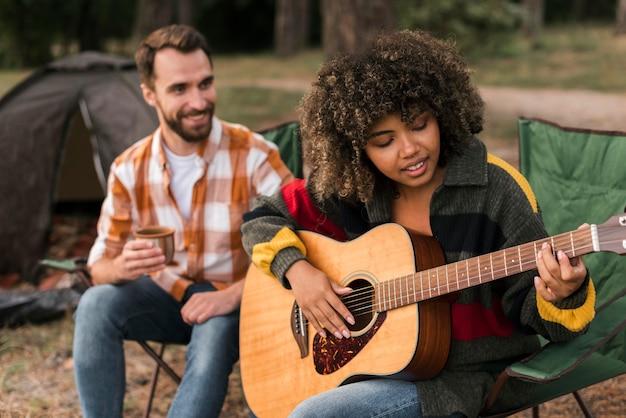 Casal tocando violão enquanto acampa ao ar livre