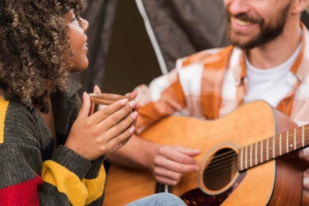 Casal tocando violão enquanto acampa do lado de fora