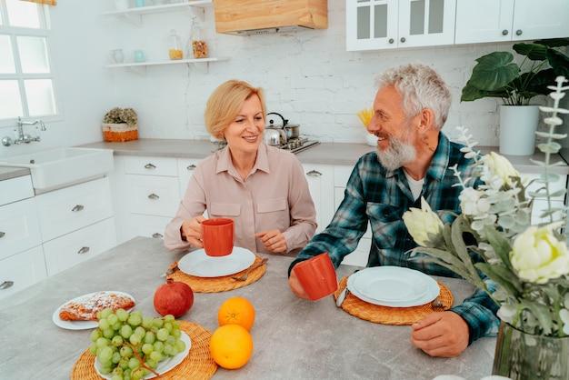 Casal toma café da manhã em casa com café e frutas